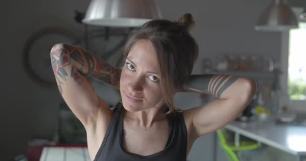 young tattooed relaxed sporty woman portrait at home. .Living room domestic training. 4k slow motion video
