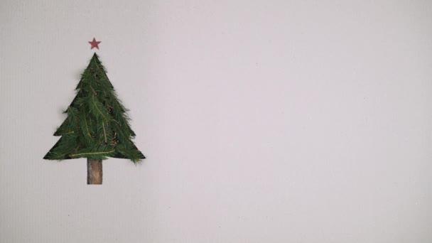 Schleife Overhead natürlichen Weihnachtsbaum Kiefer Dekoration mit blinkenden Lichtern auf Karton mit Text oder Logo kopieren space.vertical Draufsicht loop.xmas holiday season social card background.4k video
