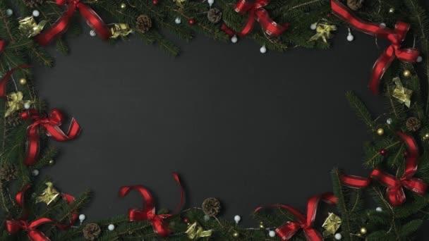 Režijní ruka uvedení krabičky na tmavě šedé pozadí s rámem dekorace šišek, červené a Zlaté stuhy. Text nebo logo kopie prostor. Vertikální pohled shora. Vánočními prázdninami sociální card.4k video