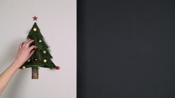 Általános személy kezét előkészítése karácsonyfa fenyőfa díszítés karton. Villogó fények, boldog karácsonyt és boldog új évet üzenetet. A holiday szezon szociális kártya background.4k videóinak függőleges felülnézet