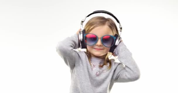 Beautiful happy fun young child blond girl with sunglasses listening to music using headphones and dancing.Person action.People video portrait isolated on white background.Medium shot.4k video.