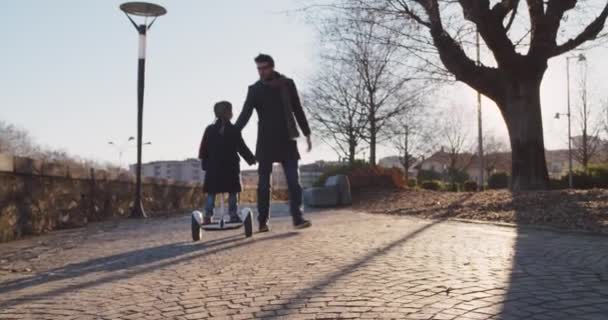 Daughter child girl learning segway riding with dad teaching in city.Modern future transport technology.Active safety family.Sidewalk urban outdoor.Warm sunset cold backlight.4k slow motion 60p video