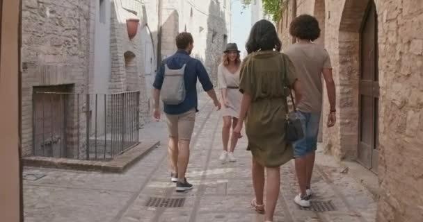 Négy boldog turista emberek séta a kis utcában látogató vidéki város Spello. back követni. Barátok olasz utazás Umbria. 4k lassú mozgás
