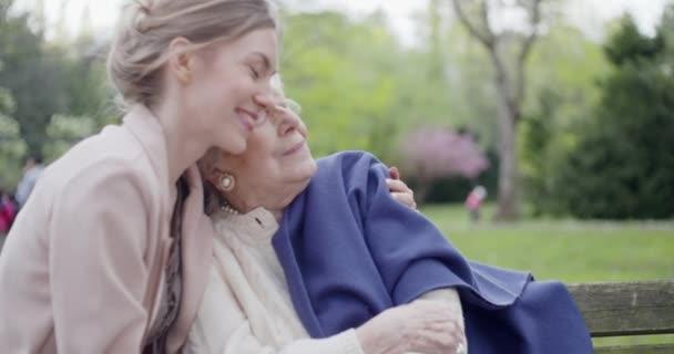 Grandmother woman kissing and hugging granddaughter at city park. Multigeneration women love holding together.White hair elderly grandma.Affection,togetherness,caring,loving,visiting,retirement