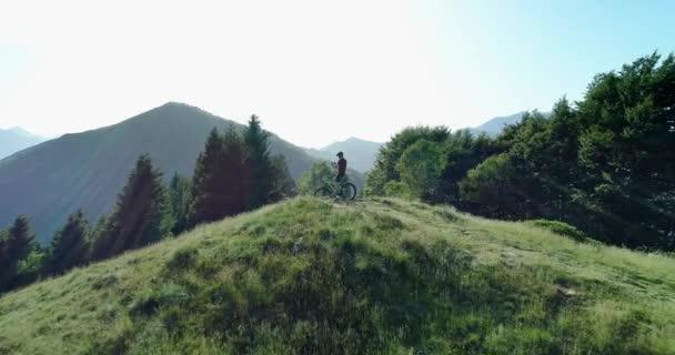 Biker si v letním slunném dnu fotografovat s anténským jezdem na horské trase smartphone. Mezivenkovský biker. Člověk používá smartphone na cyklistické anténě MTB na cestě. Muž používající mobilní