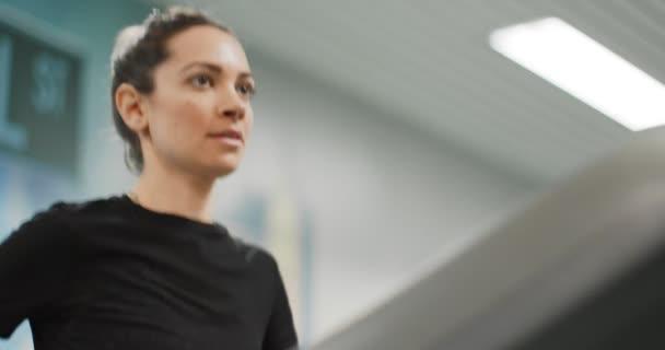 Mladá žena běží na běžeckém pásu v tělocvičně. Přední pohled zblízka, horní část těla. Školení žen ve fitness centru. Žena cvičení kardio cvičení