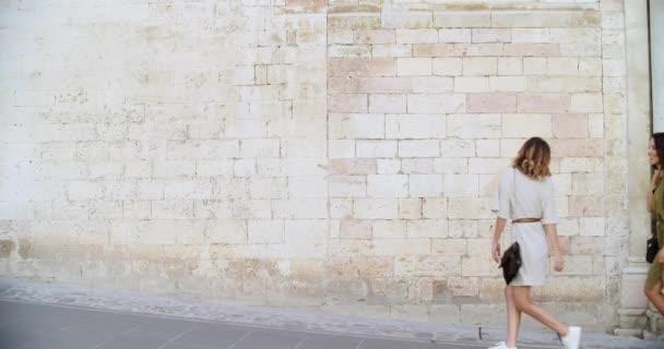 Tři lidé chodí, usmívají se a baví se u cihlové zdi ve venkovském městě Spello.Skupina turistů chůze.Boční pohled. Přátelé italský výlet v Umbria.4k zpomalení