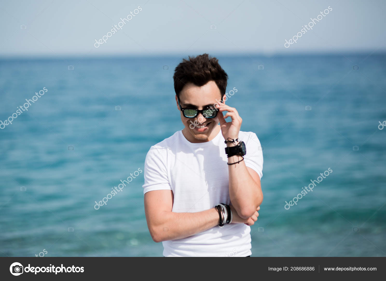 38db4f8a6bec Portrait of young handsome man in sunglasses smiling on the beach ...