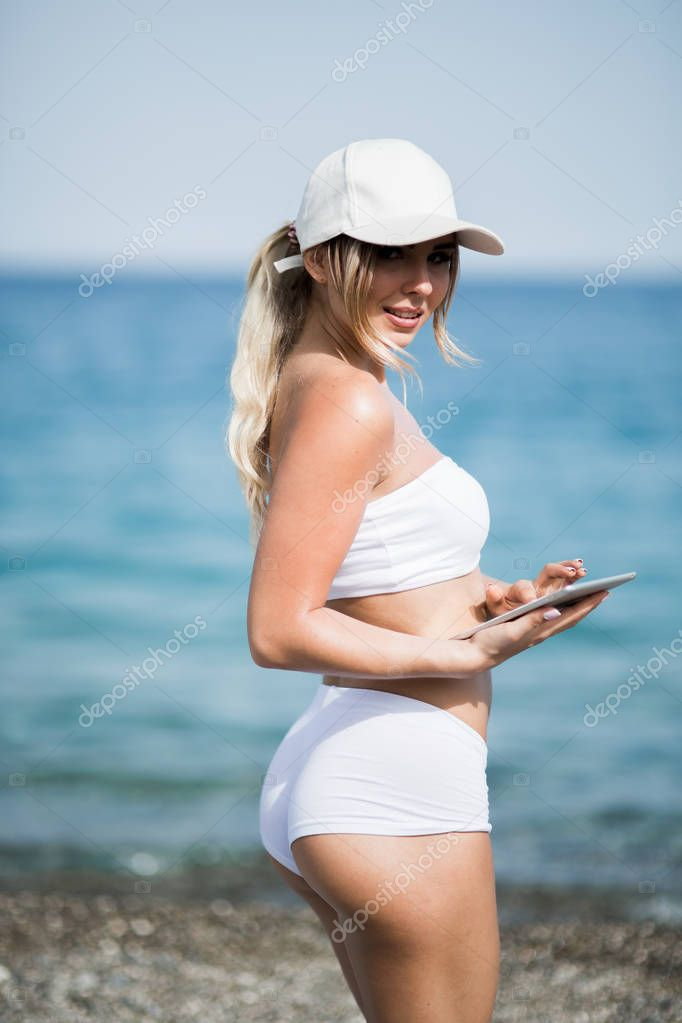 healthy gym blonde girl searches for new lifestyle fitness apps on her computer tablet