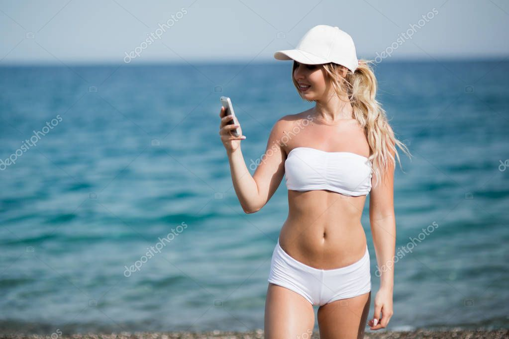 Happy pretty fitness blonde girl is showing cellphone and smiling