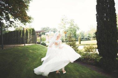 Beautiful bride in elegant white dress holding bouquet posing in park