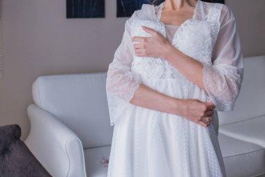 bride in peignoir holding a wedding dress