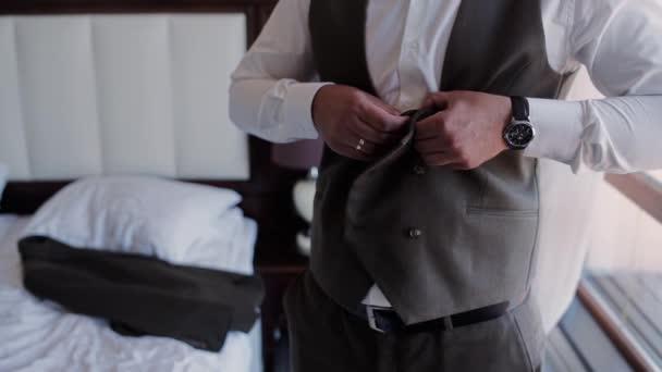 muž zapíná knoflíky na vestě obleku