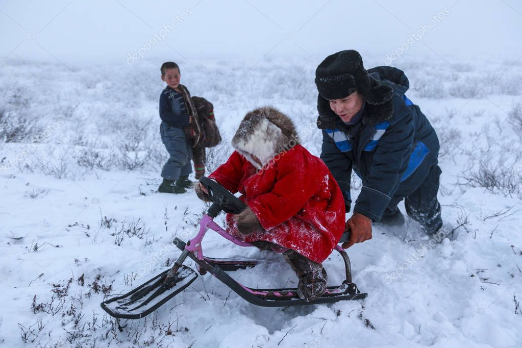 A resident of the tundra, indigenous residents of the Far North, tundra, open area, small girl ride on sledges, little girl in national red clothes