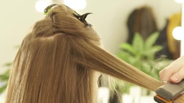 Pomocí kleští vlasy a hřeben na vlasy rovnání v salonu krásy ženské kadeřník. Detailní záběr kadeřník narovnávání vlasů v kadeřnictví v kadeřnictví