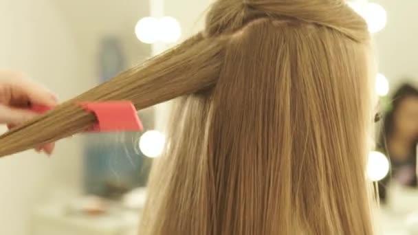 Kadeřník, česání dlouhé vlasy a rovnání kleštěmi vlasů v kadeřnictví. Zblízka ženské kadeřník narovnávání vlasů v kadeřnictví v salonu krásy
