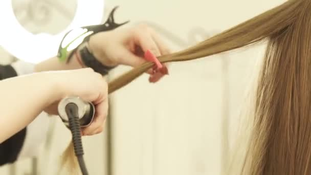Kadeřník, použití kleští vlasy a hřeben pro úpravu vlasů v salonu krásy. Detailní záběr kadeřník narovnávání dlouhé vlasy v kadeřnictví.