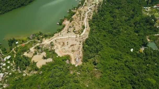 Cesta na pobřeží horské jezero a zelený les. Letecká krajina fom létající dron horské silniční a zelené tropické stromy na břehu