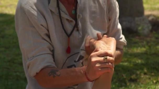 Massagiste muž dělá thajská masáž venkovní. Profesionální masér dělá protahovací masáž jóga ženské nohy. Vřelou a zdravý životní styl