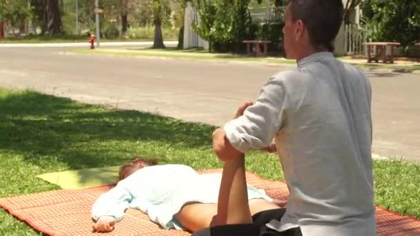 Massagiste muž dělá masáž nohou ženě k léčení a relaxaci. Venkovní masáž thajská a jógy. Koncept vřesový a harmonie