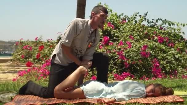 Mann-Masseur Yoga Massage, Frau liegt auf dem grünen Rasen im Freien zu tun. Traditionellen Yoga Massage als alternative Methode zur Erholung von Körper und Geist Gesundheit