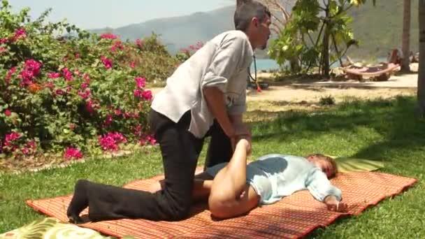 Mann massagiste tut Stretching Massage des weiblichen Beines im Freien. Frauen bekommen einen Thai-Körpermassagekurs. gesundes und harmonisches Konzept.