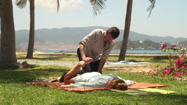 Thai massagiste nyújtó masszázs női láb szabadtéri csinál. Szakmai jóga masszázs a kikapcsolódásra, és gyógyító a test. Kezelés és a rehabilitáció koncepcióját