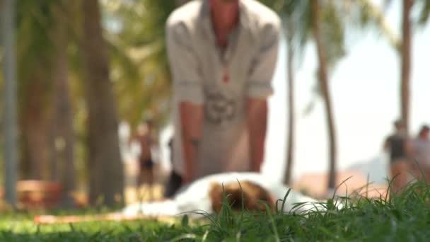 Thajská masáž terapeut dělá masáž pro ženu ležící na zelené trávě venkovní. Muž profesionální cokoliv dělat jóga masáže pro léčbu a rehabilitaci.