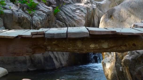 Woman legs walking on wooden bridge across stony river in mountains. Close up barefoot woman walking along hanging bridge over rapid river.