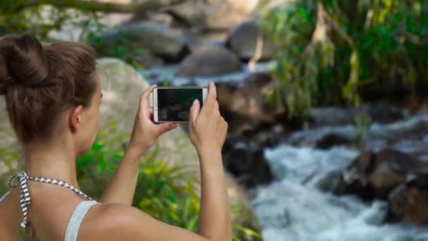 Young woman doing photo landscape on mobile phone while traveling in mountain waterfall in jungle forest. Woman tourist using smartphone for shooting video while hiking on mountain river.