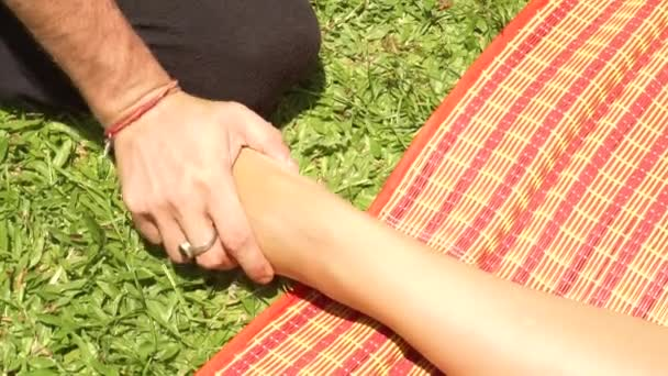 Detailní záběr masáž v thajském stylu, venkovní. Jóga massagiste dělá protahovací masáž nohou k ženě pro uzdravení a obnovu. Masáž thajská a jóga v tradiční asijské medicíně