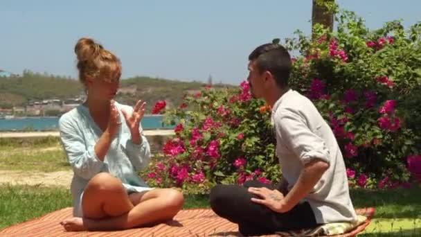 Mladá žena mluvit s učitelem jógy při odpočinku po výkonu venkovní. Muž a žena sedící na jógu lotus představují na pláži moře. Přírodní krajiny backgrond