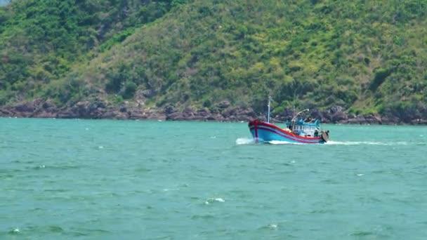 Rybářská loď plovoucí v moři na zeleném hornatém pozadí. Rybářské lodě plující v oceánu. Krásné moře a horská krajina