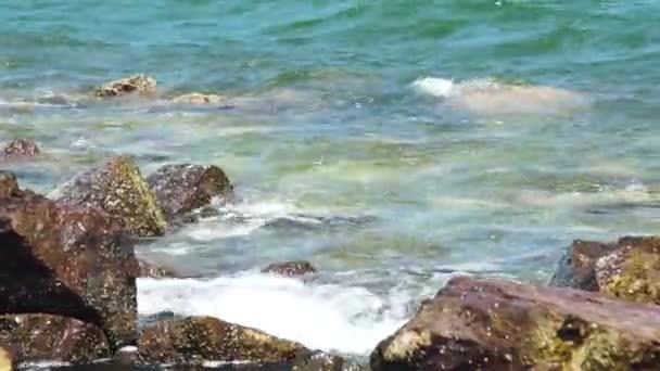 Mořské vlny stříkající na kamenité pláži. Vlny tříštící se o skalnaté pláže. Modré mořské vody a zázemí velké kameny