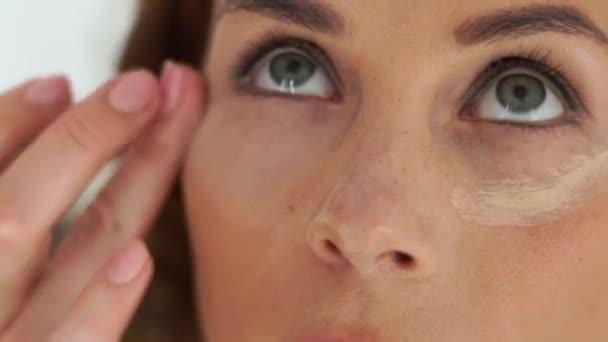Maskérka použití concealer krém na pokožku kolem očí. Zavřít až tvoří ženy v profesionální kosmetické studio. Vizážistiku dělá tvář make-up pro mladou ženu
