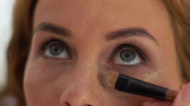 Vizážistiku použití tón krém na pleť kolem očí na modelu make-up pomocí štětce kosmetiky. Zavřít až tvoří umělec dělá make-up obličeje při tréninku v kosmetické školy