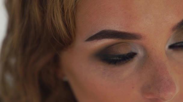 Tvář žena s dokonalým make-upem jiskřícíma očima zblízka. Portrét blikající žena s očima stylový make-up. Ženské oči a obočí zblízka