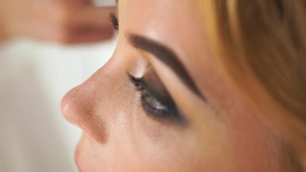 Visagiste applying mascara with brush for volume and extension eyelashes. Close up makeup model while application mascara on eyelashes. Eyelashes ans eyes makeup concept.