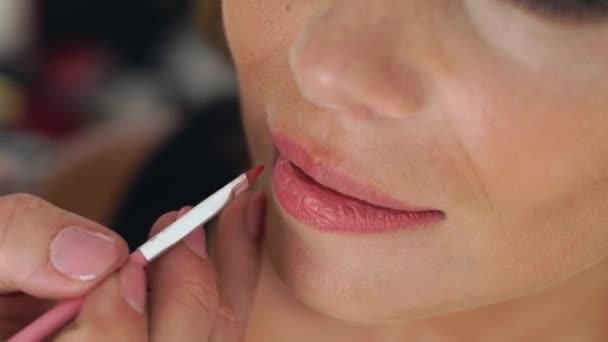 Vizážistiku pomocí štětce pro aplikaci rtěnky na rty make-up modelu. Zavřete aplikaci lesk na rty. Vizážistka dělá make-up rtů. Krása a móda