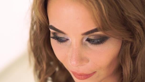 Portrét smyslná žena s tváří sexy make-up zblízka. Tvář atraktivní žena s úsměvem a pózuje pro kamery. Elegantní žena s stylový make-up a kudrnaté hnědé vlasy