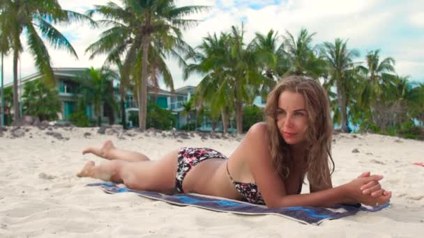 Sunbathing woman lying on towel on summer beach on luxury villa background. Attractive woman sun tanning on sandy beach while summer holiday.