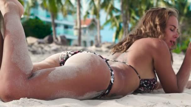 attraktive Frau im Bikini, die sich am Sommerstrand sonnt und Sand aus der Hand bläst. schöne Frau pustet Sandpuder beim Sonnenbaden am Strand.