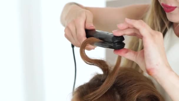 Hairdresser curling hair using hair tongs close up. Process curling brown hair with hair iron in beauty studio. Hairstylist doing stylish hairdo to long haired woman