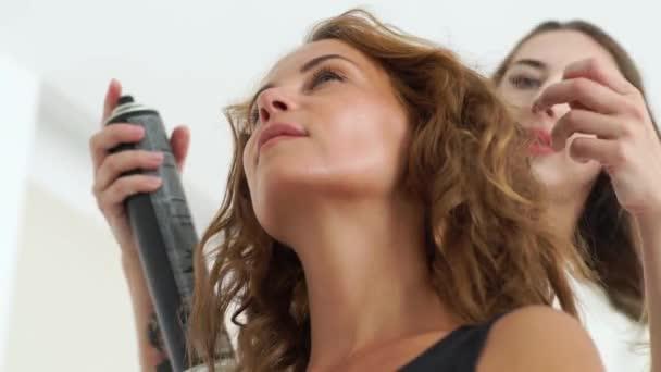 Kadeřnice, zafixujte lakem pro upevnění kudrnatý účes pro mladé ženy. Portrét hnědé vlasy žena během kadeřnictví. Detailní záběr kadeřnici takže kudrnatými chlupy na modelka.