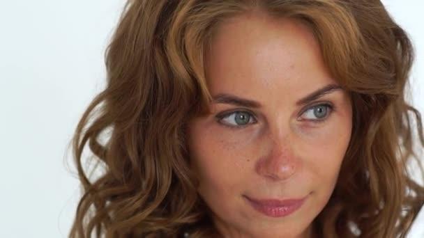 Arca vörös hajú nő, hosszú haj, a háttér fehér stúdió. Közelről portré nő szeplő bőr és göndör barna haj