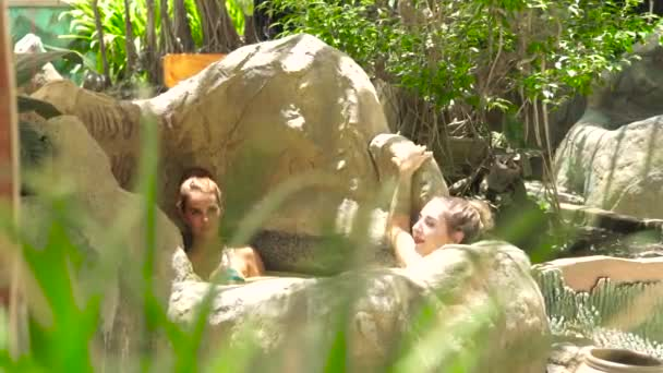 Two young woman enjoying mud bath in luxury spa center. Beautiful woman relaxing and bathing in mud spa for skin care. Body care and beauty therapy concept. Mineral mud for healthy skin.