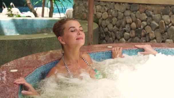 Krásná žena se těší na wellness centrum s vířivkou jacuzzi. Portrét mladé ženy relaxační v jacuzzi vaně při odpočinku v luxusní resort hotel. Kosmetické terapie a tělo péče koncept