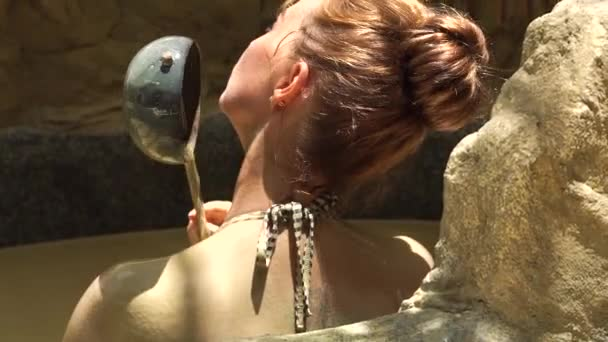 Relaxing woman bathing in mud bath in spa resort. Young woman pouring body by mud in spa bath. Beauty therapy and skin care concept. Healthy and wellness lifestyle.
