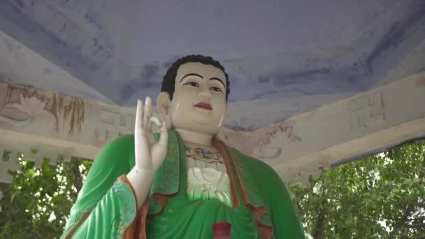 Socha Buddhy v zelených šatech v buddhistická pagoda zblízka. Socha sedícího Buddhy v starověkého chrámu. Asijská náboženství a kultura