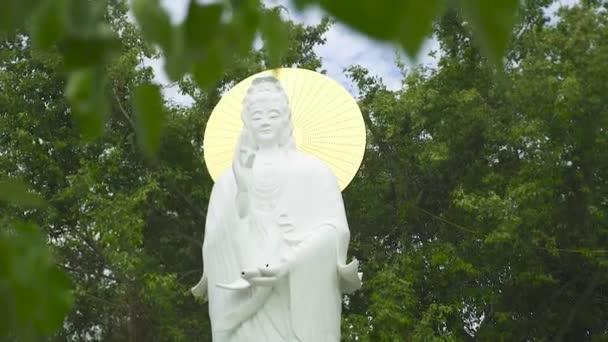 Socha žena Buddhy v buddhistickém chrámu na pozadí zelených rostlin a stromů. Starobylé buddhistické sochy v náboženské pagoda